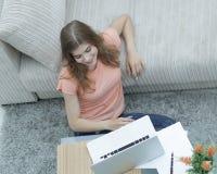 Студент девушки работая на компьтер-книжке сидя на ковре около софы Стоковое фото RF
