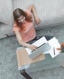 Студент девушки работая на компьтер-книжке сидя на ковре около софы Стоковое Изображение