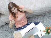 Студент девушки работая на компьтер-книжке сидя на ковре около софы Стоковые Изображения