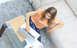 Студент девушки работая на компьтер-книжке сидя на ковре около софы Стоковое Фото