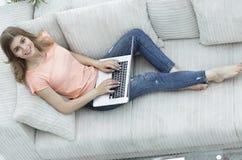Студент девушки работая при компьтер-книжка сидя на софе и смотря камеру Стоковая Фотография