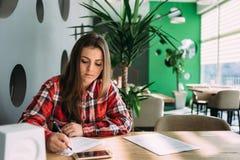 Студент девушки сидя в ярком сочинительстве кафа что-то на бумаге Стоковая Фотография RF