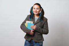 Студент девушки со стогом книг в ее руках смотрит камеру и улыбки на светлой предпосылке стоковая фотография