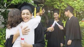 Студент девушки с мантиями градации и шляпа обнимают родителя внутри Стоковая Фотография RF
