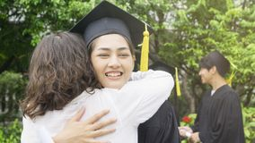 Студент девушки с мантиями градации и шляпа обнимают родителя внутри Стоковое Изображение RF