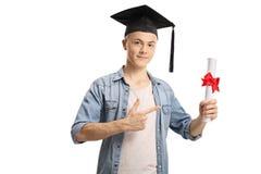 Студент держа диплом и указывать стоковое фото rf