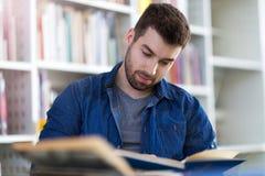 Студент изучая в библиотеке стоковое изображение