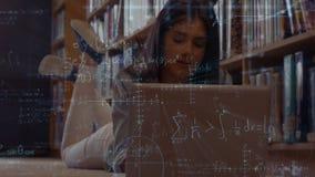 Студент используя ее ноутбук в библиотеке видеоматериал