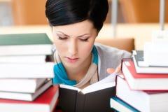 Студент книги чтения сидя на столе стоковое изображение rf