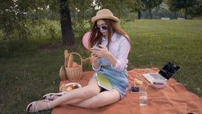 Студент колледжа имбиря в соломенной шляпе и солнечных очках отправляет СМС и изучает в парке сток-видео