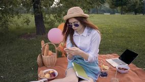 Студент колледжа имбиря в текстах соломенной шляпы и солнечных очков и усмехаться в парке сток-видео