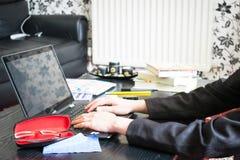 Студент маленькой девочки работая или изучая дома и писать примечания и делая домашнюю работу путем использование портативного ко стоковое изображение