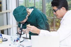 Студент-медик и ассистент по исследованиям молодой женщины с микроскопами стоковое изображение rf