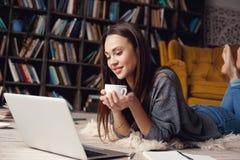 Студент молодой женщины в серии библиотеки дома лежа наблюдая стоковые фото