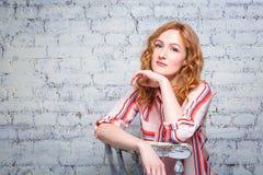 Студент молодой женщины портрета красивый с красными вьющиеся волосы и веснушками на ее стороне сидя на деревянном стуле на кирпи стоковое фото rf