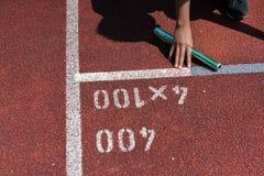 Студент подготавливает к выходить начинать для эстафетного бега на школу Стоковые Изображения RF