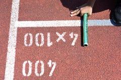 Студент подготавливает к выходить начинать для эстафетного бега на школу Стоковое Фото