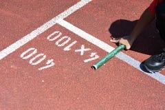 Студент подготавливает к выходить начинать для эстафетного бега на школу Стоковые Фотографии RF