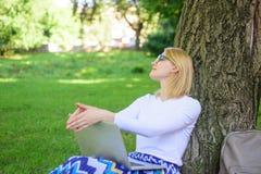 Студент подготавливает проект Исследование парка компьтер-книжки женщины онлайн Девушка сидит трава с тетрадью Девушка пользуется стоковое фото