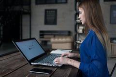 Студент подготавливая для классов занимаясь серфингом интернет на ее компьтер-книжке сидя на таблице в ультрамодном кафе стоковое изображение