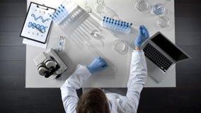 Студент принимая реагенты и наблюдая химическое experiement в подоле, взгляд сверху стоковое фото
