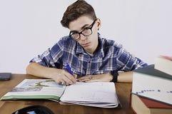 Студент при стекла делая домашнюю работу Стоковые Фотографии RF