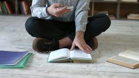 Студент при телефон делая шпаргалку в библиотеке сток-видео