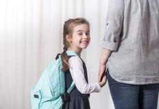 Студент родителя и начальной школы пойти рука об руку стоковые изображения