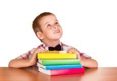 Студент сидит на таблице при изолированные книги на белизне Стоковые Изображения RF