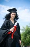 студент студент-выпускника диплома плаща счастливый Стоковое Фото