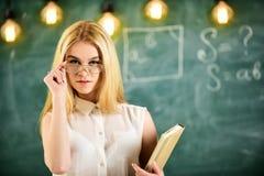 Студент, учитель смотрит уверенно в eyeglasses, стойке в классе, доске на предпосылке, defocused привлекательностей стоковое фото rf