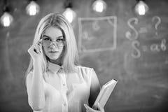 Студент, учитель смотрит уверенно в eyeglasses, стойке в классе, доске на предпосылке, defocused привлекательностей стоковое фото