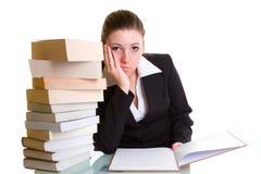 Студент учя с кучей книг на столе Стоковые Фото