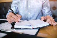 Студент человека пишет информацию от портативной таблетки пока prepar Стоковое Изображение RF