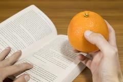 Студент читает пока ест апельсин на деревянной таблице Стоковое Изображение