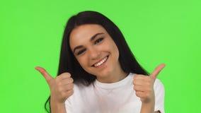 Студия близкая вверх счастливой девушки показывая большие пальцы руки вверх на зеленой предпосылке акции видеоматериалы