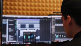 Студия звукозаписи звукооператора дома смотрит экран с цифровым аудио местом для работы пока смешивающ и управляющ musi утеса поп сток-видео