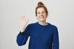 Студия сняла дружелюбной красивой кавказской девушки с красными волосами и веснушками, нося вскользь свитером, развевая ладонь по Стоковое Изображение RF
