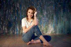 Студия сняла молодой усмехаясь девушки в джинсах и футболки сидя на поле Яркий солнечный свет, положительные эмоции стоковые фото