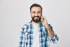Студия сняла привлекательного жизнерадостного европейского парня с бородой и усиком, говорящ через smartphone и усмехающся обширн стоковая фотография rf