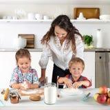 Студия сняла семьи в кухне дома Небольшие дети, девушка и мальчик, учат сделать крены теста с их матерью или стоковая фотография