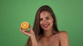 Студия сняла шикарной счастливой женщины усмехаясь держащ половину апельсина стоковая фотография