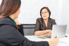 Студия снятая азиатской, старшей коммерсантки с ноутбуком, сидя с 2 молодыми штатами в комнате правления в офисе, босс делая серь стоковые фото