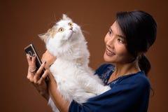 Студия снятая красивой азиатской женщины против коричневой предпосылки стоковая фотография
