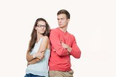 Студия снятая рассерженных пар нося случайные одежды стоя спина к спине хмурящся их стороны Разладка в стоковые фото
