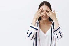 Студия снятая симпатичного очаровательного и дружелюбного молодого работника офиса в striped блузке, покрывающ глаза с ладонями и стоковое изображение rf