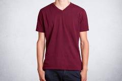 Студия снятая случайное темного - красная футболка, представленный над белой предпосылкой Деталь хлопка одежд несенных на худеньк стоковые фото