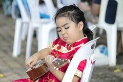 Стул девушки сидя с жизнерадостной серьезной играя гавайской гитарой Стоковая Фотография RF