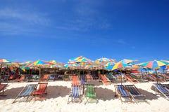 Стул пляжа и цветастый зонтик пляжа Стоковая Фотография