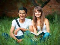 2 студента в парке на траве с книгой outdoors Стоковое фото RF